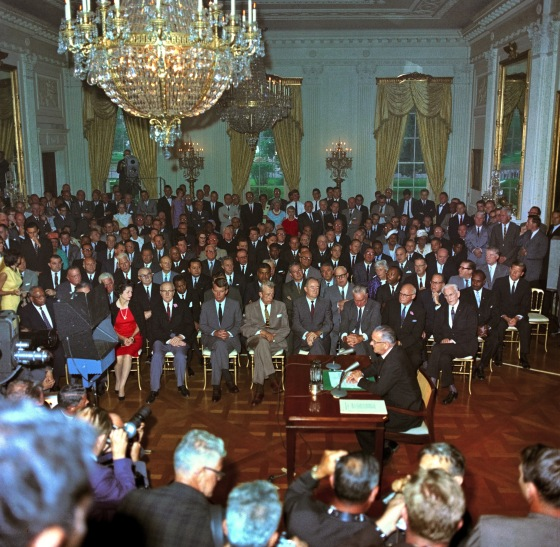 "President Lyndon B. Johnson at the signing the Civil Rights Act of 1964, of which Title VII is a subchapter. People watching include then Attorney General Robert Kennedy, Senator Hubert Humphrey, First Lady ""Lady Bird"" Johnson, Rev. Martin Luther King, Jr., FBI Director J. Edgar Hoover, & Speaker of the House John McCormack. Television cameras are broadcasting the ceremony. Source: LBJ Presidential Library."